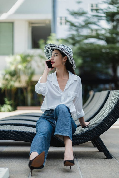 Stylish young ethnic woman talking on smartphone sitting on sunbed