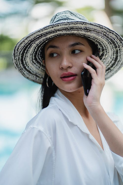Side view of gorgeous young Asian female in trendy hat and white shirt talking on mobile phone and looking over shoulder near outdoor pool