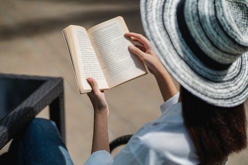 Unrecognizable woman reading novel on terrace