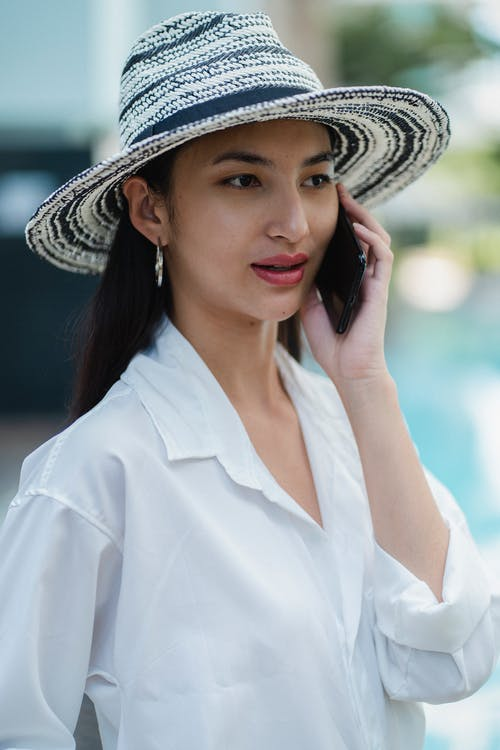Concentrated young Asian lady in white shirt and straw hat talking on cellphone and looking away on sunny day