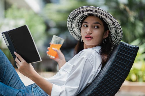 Concentrated young ethnic female drinking juice and reading diary sitting on veranda