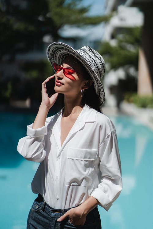 Content young Asian female tourist having phone conversation at poolside