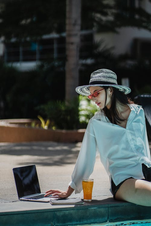 Self employed ethnic woman working on netbook near pool