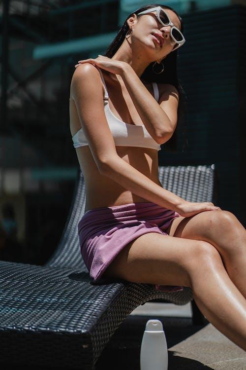Slim woman spreading cream on body sitting on sunbed