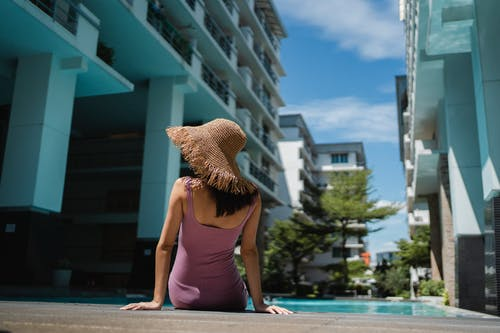Woman resting on poolside of tropical resort