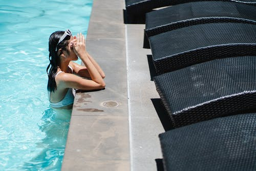 From above side view of female traveler in swimwear resting in swimming pool during summer holidays