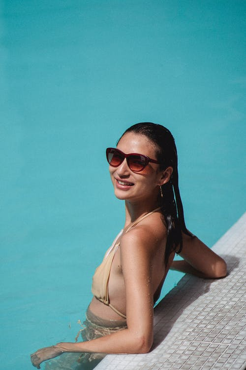 Relaxed young ethnic female standing in pool in sunlight