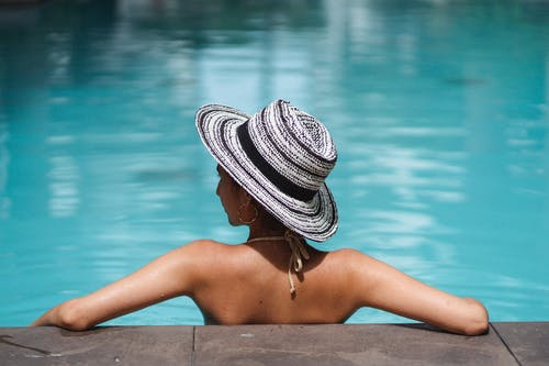 Anonymous slim lady resting in pool water and looking away