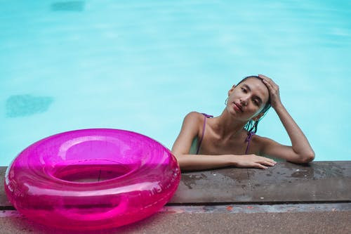 Alluring young ethnic woman resting in pool water near swim ring