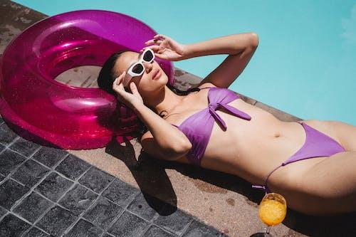Sensual young ethnic woman adjusting sunglasses while sunbathing on pool border