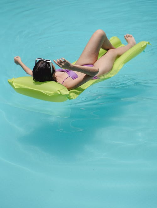 Full body of unrecognizable female tourist in swimsuit and sunglasses lying on inflatable green mattress in pool while relaxing during summer vacation