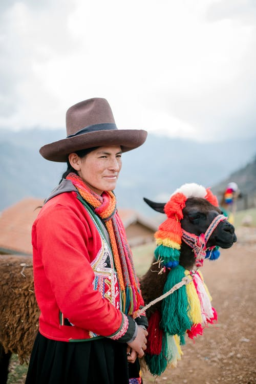 Quechua woman in traditional outfit standing on rural road with cute lama