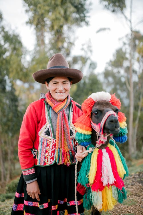 Positive adult native Peruvian female in national dress and hat smiling while standing near trees with cute lama decorated with colorful traditional tassels