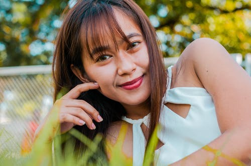 Cheerful Asian female looking at camera while lying on grassy ground near metal fence and tall trees on blurred background