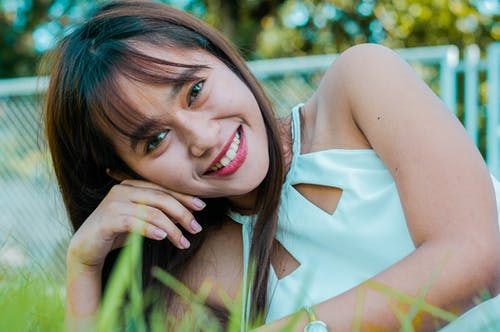 Cheerful young Asian female looking at camera while lying on green grass on street with metal fence on blurred background