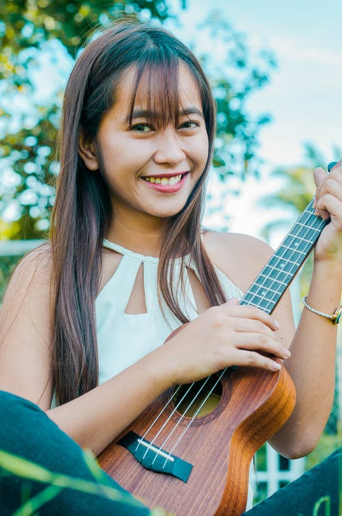 Content Asian female musician playing ukulele and looking at camera while sitting on grassy lawn near trees on sunny summer day