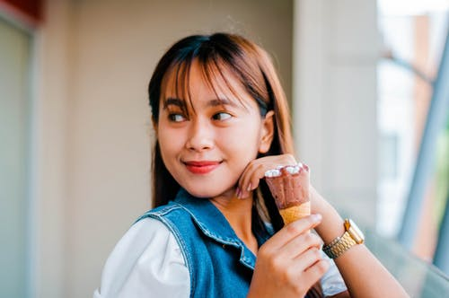 Content Asian woman with ice cream on balcony