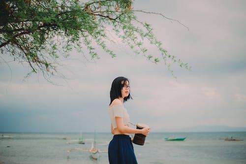 Женщина в белой рубашке и синей юбке стоит на пляже