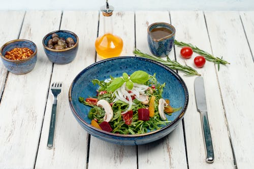 Vegetable Salad on Blue Ceramic Bowl Beside Stainless Steel Fork and Knife on Brown Wooden Table