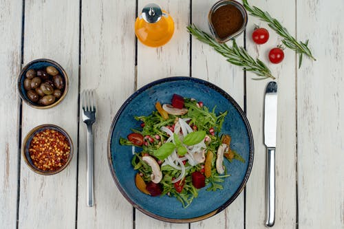 Vegetable Salad on Blue Ceramic Plate Beside Stainless Steel Fork and Knife