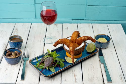 Fried Food on Green and White Ceramic Plate Beside Red Wine Glass