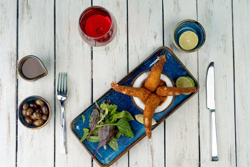 Fried Chicken on Blue and Green Floral Ceramic Plate Beside Red Ceramic Mug