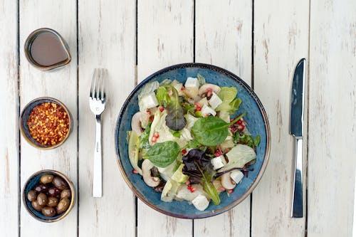 Vegetable Salad on Blue Ceramic Bowl Beside Stainless Steel Fork and Knife