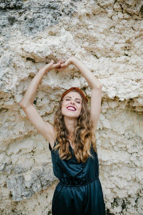 站立反對石形成的時髦的快樂的婦女