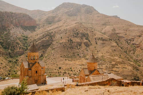 From above of travelers walking near old cathedrals located in mountainous area in sunny day
