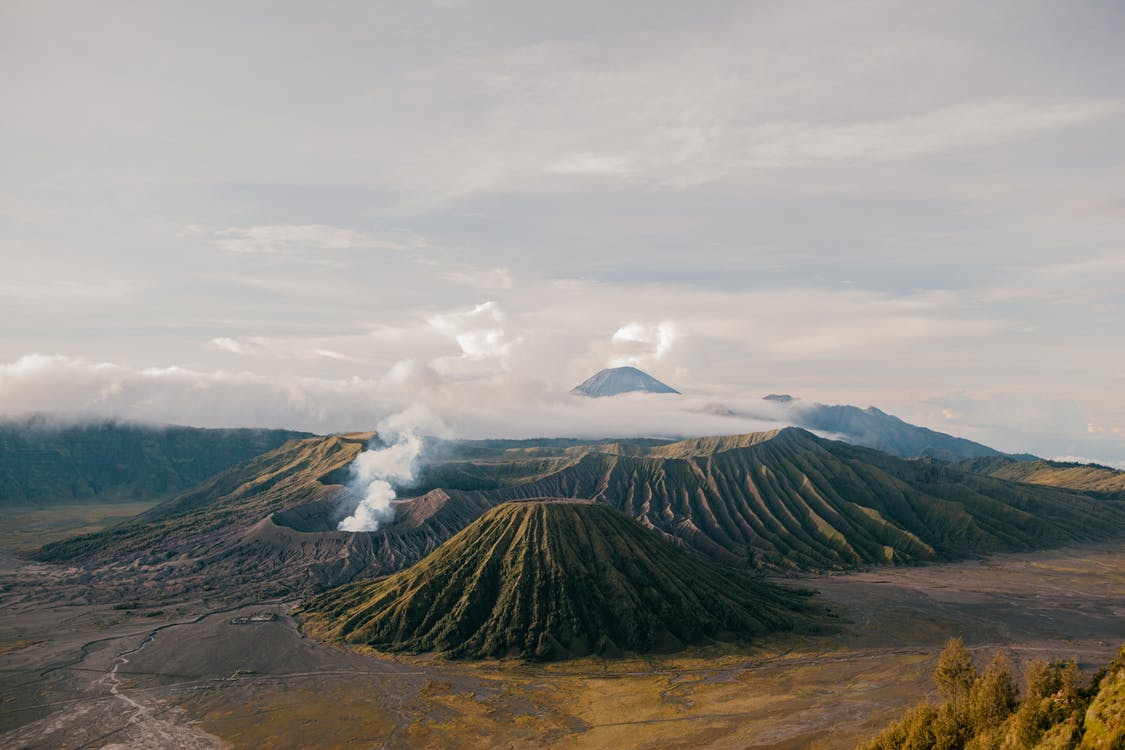 From above of picturesque scenery of volcanic mountains located in vast desolate terrain under cloudy sky