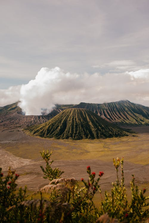 From above of rough rocky steaming volcanic highland area located in vast terrain under cloudy sky
