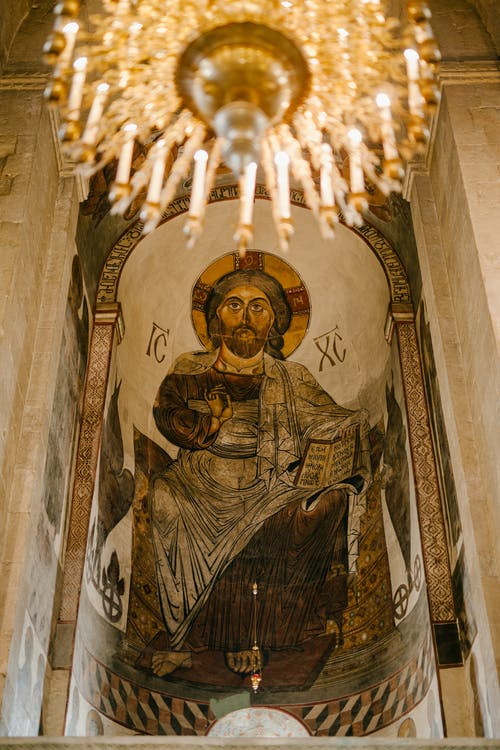 From below of painting of Jesus Christ on stone wall under chandelier in Christian cathedral