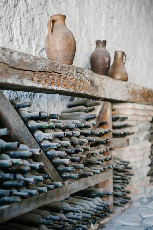 Wooden shelves with dusty glass bottles of wine
