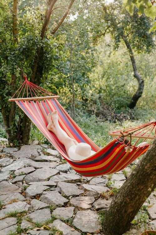 Женщина отдыхает в гамаке среди зеленых деревьев