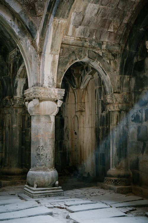 Interior of ancient stone masonry palace with arched passages and ornamental columns on shabby cement floor with ray of light