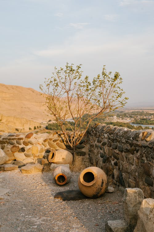 Clay jugs near stone wall of ancient building