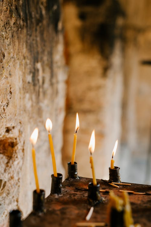 Burning flame of candles placed on shabby surface of ancient sacred place with stone walls