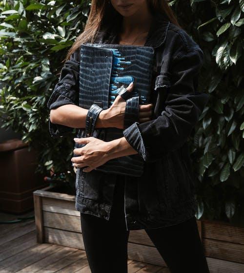 Woman in Black Leather Jacket Standing on Brown Wooden Floor
