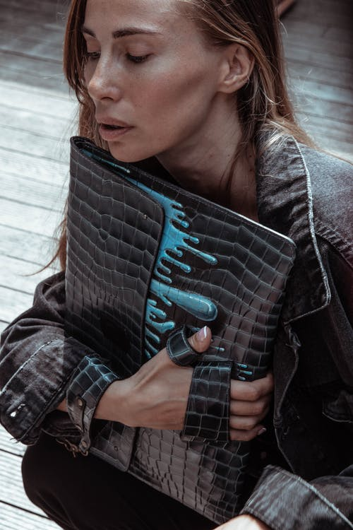 Woman in Black Leather Jacket Holding Blue and Black Leather Bag