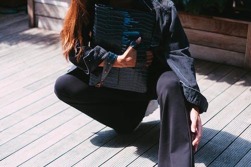 Woman in Black Jacket and Black Pants Sitting on Wooden Floor