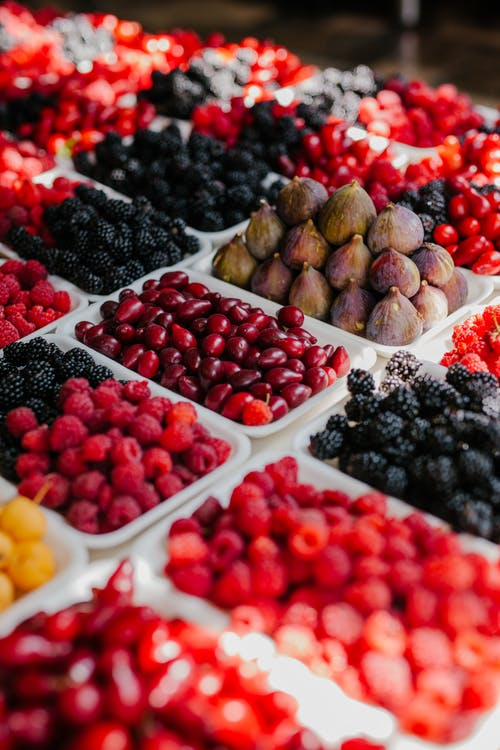 From above of assorted ripe blackberries figs raspberries and fruits of dog rose at counter