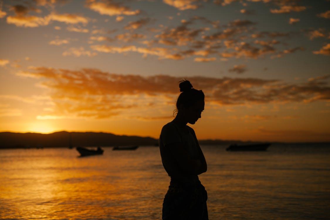 Traurige Frau, Die An Der Küste Des Meeres Bei Sonnenuntergang Steht