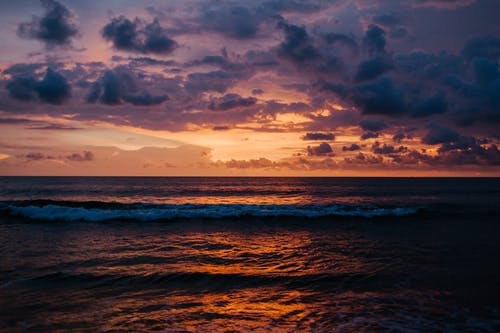 Picturesque view of foamy waves of endless rippling sea under cloudy sky at sundown