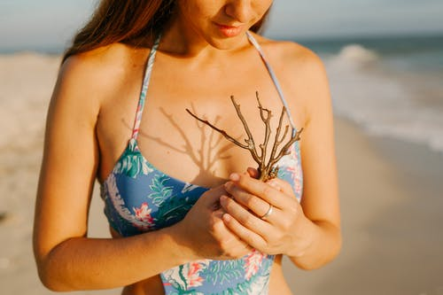 Crop female traveler in swimwear standing on sandy coast with piece of coral during vacation in tropical country