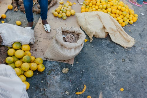 From above of crop faceless seller near pile of ripe oranges on ground and bag of grains at bazaar