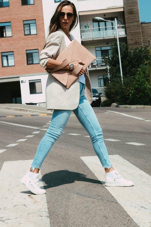 Stylish woman with handbag walking on crosswalk