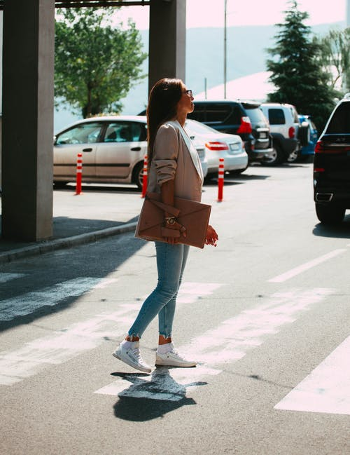 Young stylish lady with bag crossing road