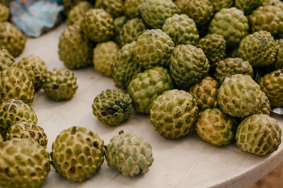 From above of stack of fresh ripe exotic globe artichokes placed on table in countryside