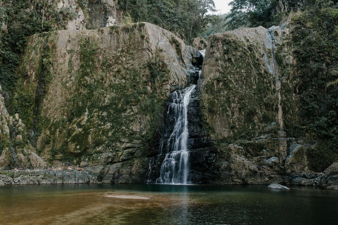 Fast waterfall between rough mountains near pure pond
