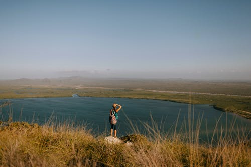 Back view of anonymous female backpacker admiring rippled river from mountain with faded grass on foggy day